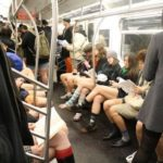 Women and men with no pants on riding a subway train