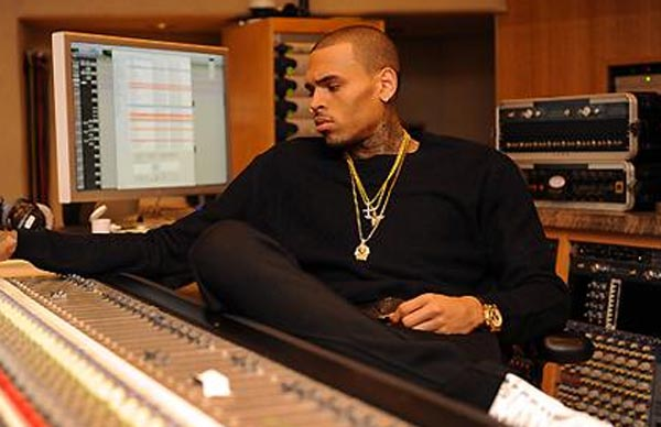 Singer Chris Brown at console at recording studio