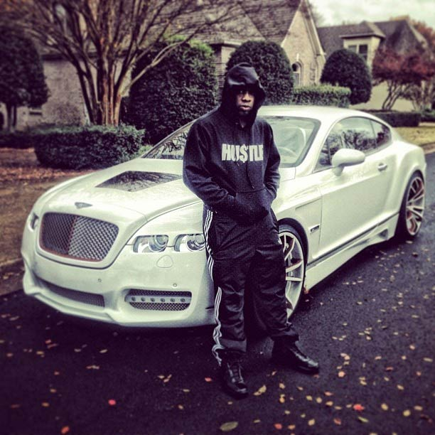Yo Gotti posing next to CMG White Bentley Coupe