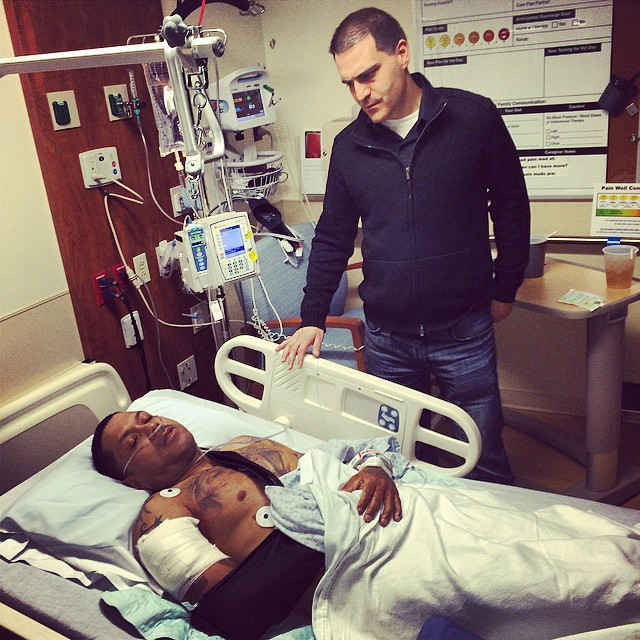 Benzino lays in hospital bed as Dave Mays stands near him