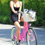 Photo of Miley Cyrus upskirt in black mini dress on bike