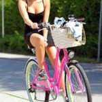 Photo of Miley Cyrus in black mini dress on bike